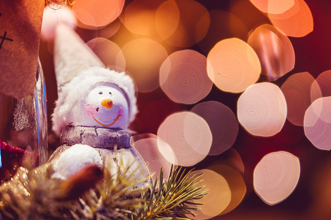 Christmas ornament of a snowman sitting in a tree.