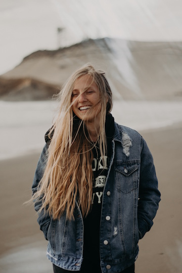Woman walking on a beach, smiling and expressing happiness.