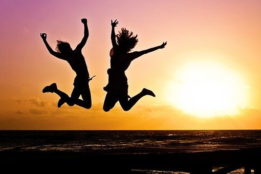 A silhouette of two woman jumping in joy, there is a sunset in the background.