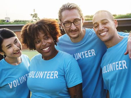 Group of 4 friends smiling, they are all wearing blue t shirts that say volunteer.