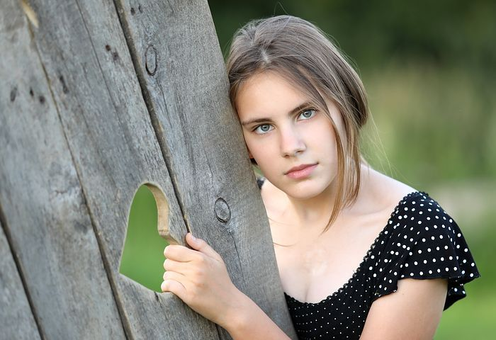 Young woman holding onto a fence with a heart etched into it.