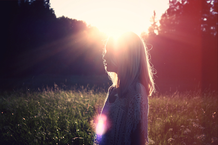 A silhouette of a woman in a field, the sun is creating the silhouette.