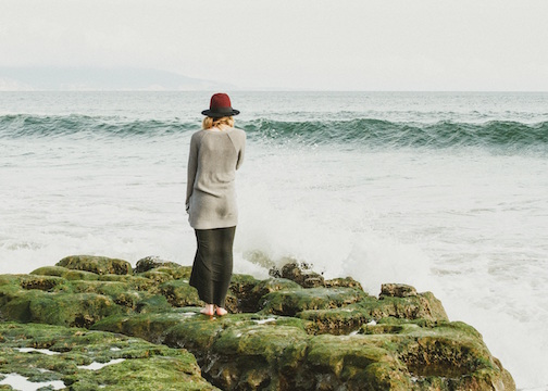 Woman standing on a rocky beach viewing the surf.