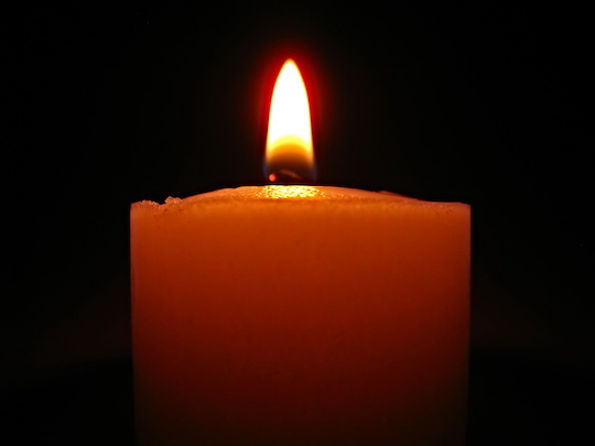 A lone, lit candle with a dark background.