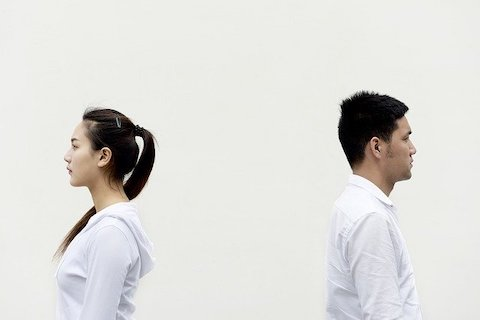 A man and a woman facing back to back wearing white clothes in front a white wall.