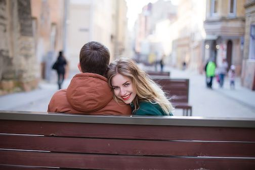 A couple sitting on a bench in a city, the woman is looking at the camera and smiling.