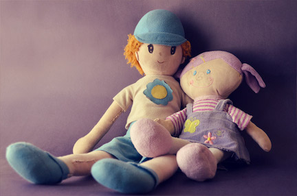 Two Raggedy Anne style dolls placed next to one another, one has blue colors one has pink.