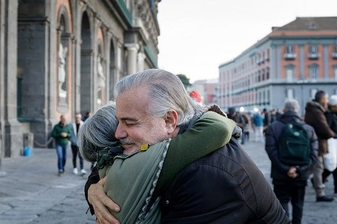 Two older people embracing each other with a hug in a downtown area.