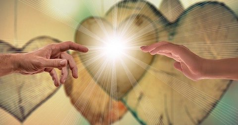 A single male hand with its finger pointing toward a female outreaching hand as light exudes from the space between them in front of multiple hearts.