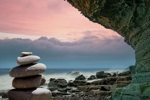 View of a cliff with an ocean sunset in the background, neatly stacked rocks are the focal point.