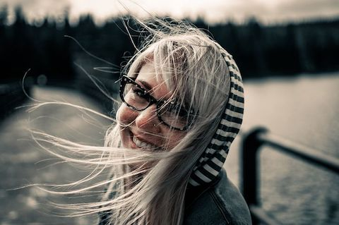 Woman with glasses smiling, the breeze is blowing her hair about.