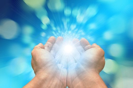 Two adjoined hands exuding light from center of palms in front of a bright blue background.