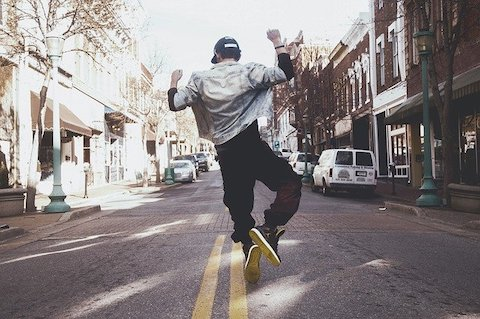 Rear view of a young man jumping up and clicking his heals together in a downtown setting.