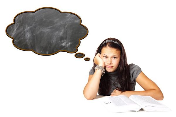 A person sitting in front of an open book, thinking and expressing the frustration of procrastination.