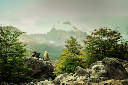 Hiker relaxing on a rock as they view a far away mountain.