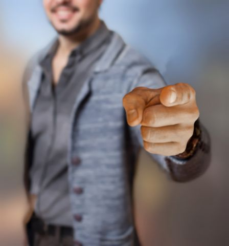 Man smiling and pointing his finger directly into the camera.
