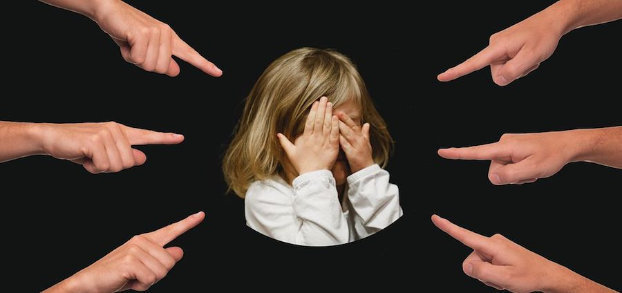 Six different hands pointing their fingers at a little girl who is crying, illustrating projection.