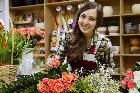 Female florist in a flower shop smiling.