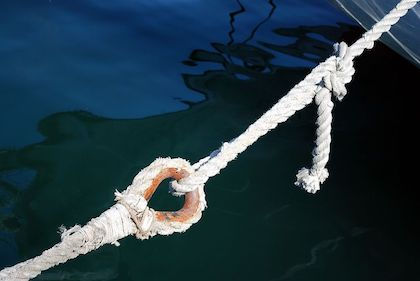 Two looped ropes attached to one another, over water.