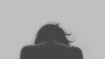 Black and white rear view of a woman sulking with her head down.