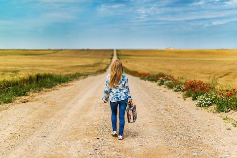 Woman walking alone with a small briefcase on a rural, dirt road.
