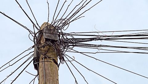 Close up and upward view of telephone pole with a disorganized cluster of wires.