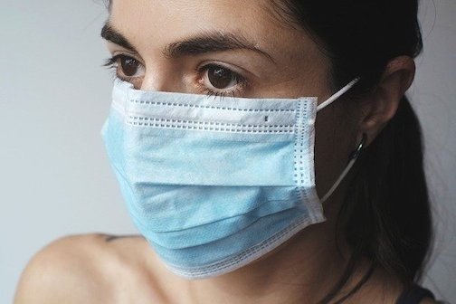Close up picture of a woman wearing a disposable face mask.