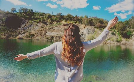 Rear view of a woman holding her arms out in front of a beautiful lake, expressing freedom.