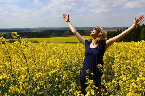 Woman in a sundress smiling and embracing the sky with open arms, in a field of yellow flowers.